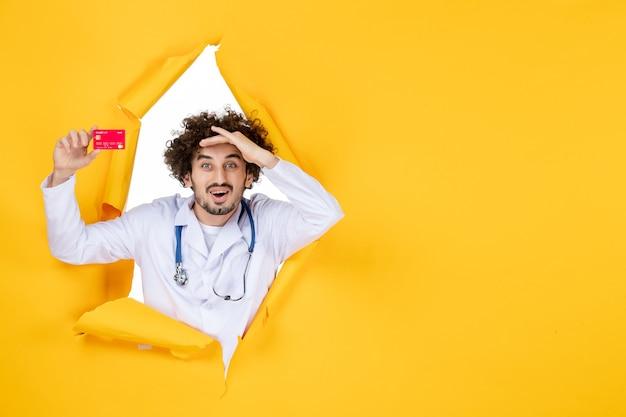 Vooraanzicht mannelijke arts in medisch pak met rode bankkaart op gele kleur geneeskunde ziekenhuis gezondheidsvirus medic