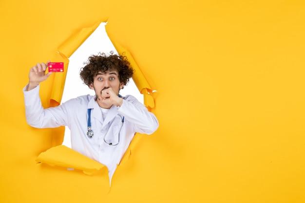 Vooraanzicht mannelijke arts in medisch pak met rode bankkaart op gele kleur geneeskunde ziekenhuisziekte gezondheidsvirus medic geld