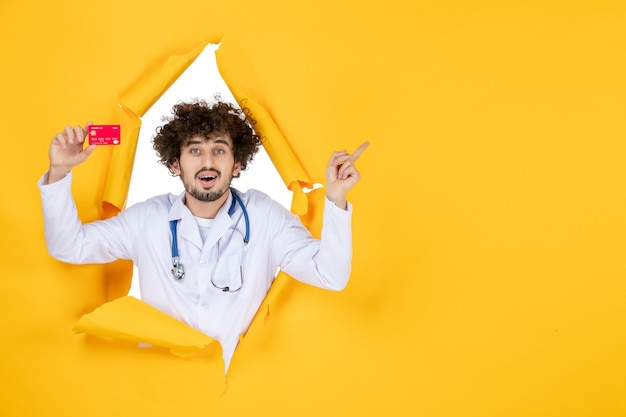 Vooraanzicht mannelijke arts in medisch pak met rode bankkaart op gele kleur geneeskunde ziekenhuisziekte gezondheidsvirus medic