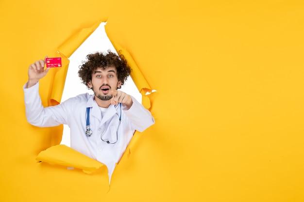 Vooraanzicht mannelijke arts in medisch pak met rode bankkaart op gele kleur geneeskunde ziekenhuisziekte virus medic gezondheid
