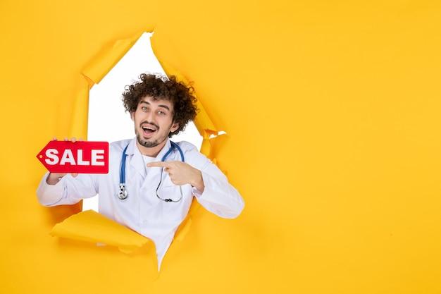 Vooraanzicht mannelijke arts in medisch pak met rode verkoop schrijven op gele dokter kleur gezondheidsziekte ziekenhuis geneeskunde
