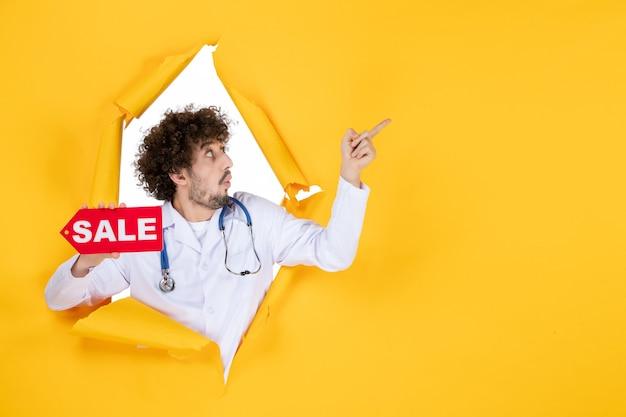 Vooraanzicht mannelijke arts in medisch pak met rode verkoop schrijven op gele dokterskleur gezondheidsziekte winkelend ziekenhuis