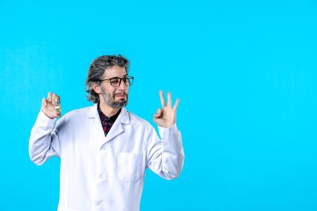 Vooraanzicht mannelijke arts in medisch uniform die een flesje op de blauwe houdt