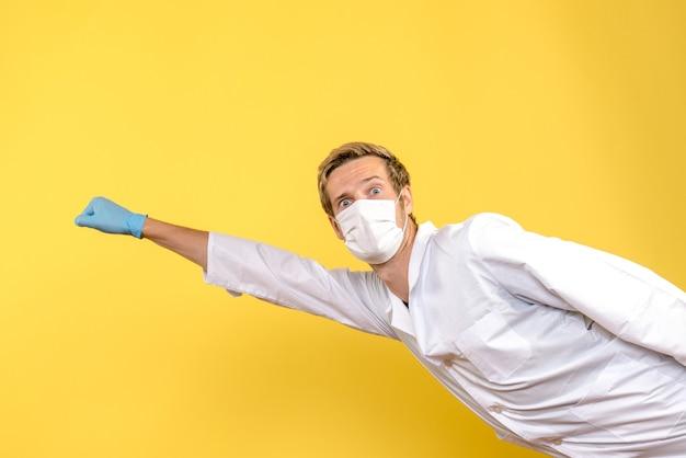 Vooraanzicht mannelijke arts in superman pose op gele achtergrond covid pandemie gezondheid medic