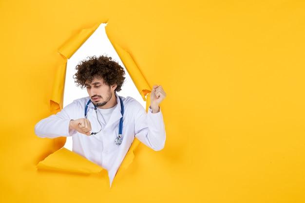 Vooraanzicht mannelijke arts in wit medisch pak die de tijd controleert op geel gescheurd gezondheidsgeneeskunde virus kleur medic ziekenhuis