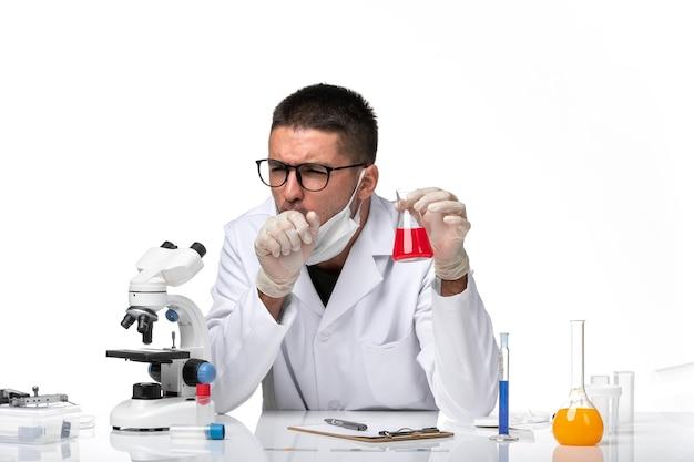 Vooraanzicht mannelijke arts in wit medisch pak en met masker met rode oplossing op een witte ruimte