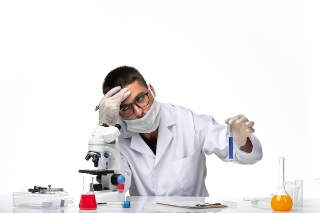 Vooraanzicht mannelijke arts in wit medisch pak en met masker moe van owrk op witte ruimte