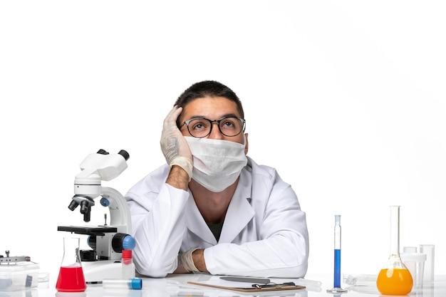 Vooraanzicht mannelijke arts in wit medisch pak en met masker stressvol poseren op witte ruimte
