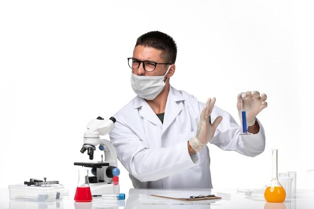 Vooraanzicht mannelijke arts in wit medisch pak en met masker werken met oplossing op witte ruimte