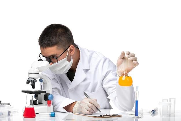Vooraanzicht mannelijke arts in wit medisch pak en met masker werken met oplossingen op witte ruimte