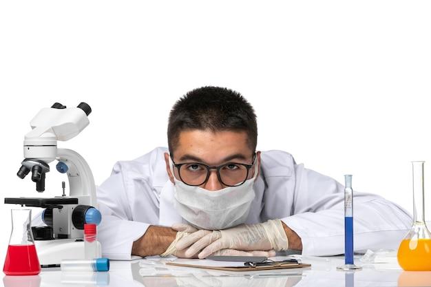 Vooraanzicht mannelijke arts in wit medisch pak en met masker zo moe van het werk aan witte ruimte