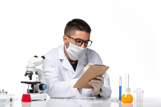 Vooraanzicht mannelijke arts in wit medisch pak het schrijven van notities op een witte ruimte