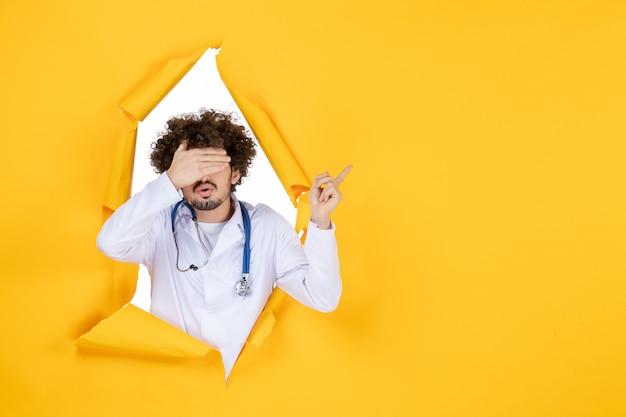 Vooraanzicht mannelijke arts in wit medisch pak met bedekt gezicht op geel gescheurd gezondheidsgeneeskunde virus kleur medisch ziekenhuis