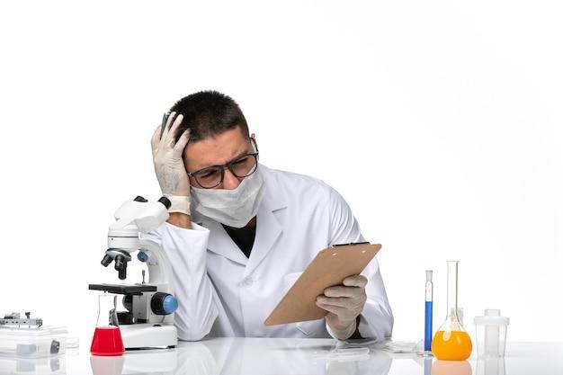 Vooraanzicht mannelijke arts in wit medisch pak met masker vanwege covid notities schrijven over witte ruimte