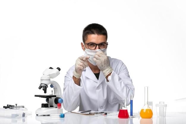 Vooraanzicht mannelijke arts in wit medisch pak met masker vanwege covid op witte ruimte