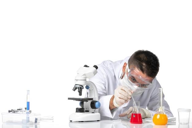 Vooraanzicht mannelijke arts in wit medisch pak met masker vanwege covid werken met oplossingen op lichte witte ruimte