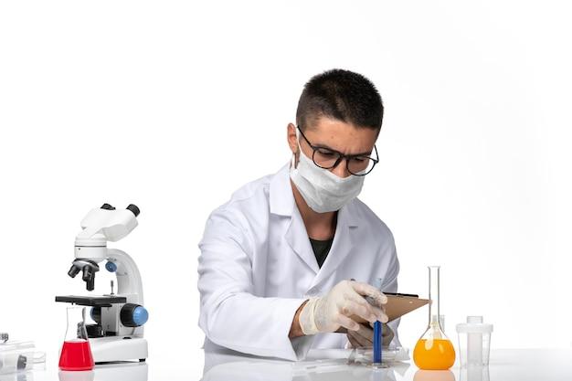 Vooraanzicht mannelijke arts in wit medisch pak met masker vanwege covid werken met oplossingen op witte ruimte