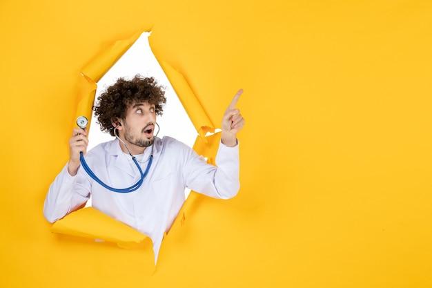 Vooraanzicht mannelijke arts in wit medisch pak met stethoscoop op geel gescheurd medic health color medicine virus