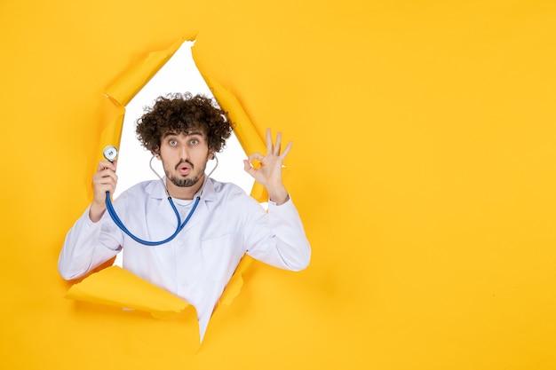 Vooraanzicht mannelijke arts in wit medisch pak met stethoscoop op geel gescheurd medic ziekenhuis gezondheidskleur geneeskunde virus