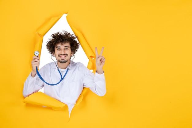 Vooraanzicht mannelijke arts in wit medisch pak met stethoscoop op gele gescheurde kleur medic ziekenhuis gezondheid geneeskunde virus