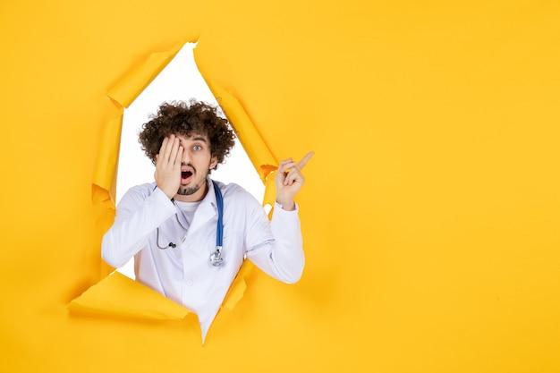 Vooraanzicht mannelijke arts in wit medisch pak op geel gescheurd gezondheidsgeneeskunde virus kleur medisch ziekenhuis