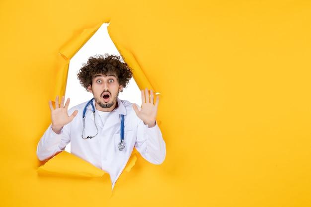 Vooraanzicht mannelijke arts in wit medisch pak op geel gescheurd gezondheidsziekenhuis verpleegster geneeskunde virus kleur medic