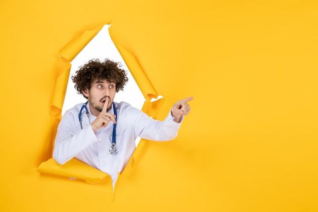 Vooraanzicht mannelijke arts in wit medisch pak op geel gescheurd medicijnkleur medic virus ziekenhuis