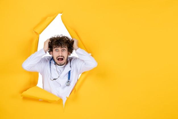 Vooraanzicht mannelijke arts in wit medisch pak op geel gescheurd virus medic kleur ziekenhuis geneeskunde gezondheid