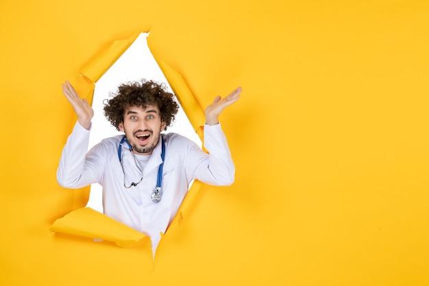 Vooraanzicht mannelijke arts in wit medisch pak op gele gescheurde virus medic kleur ziekenhuisgezondheid
