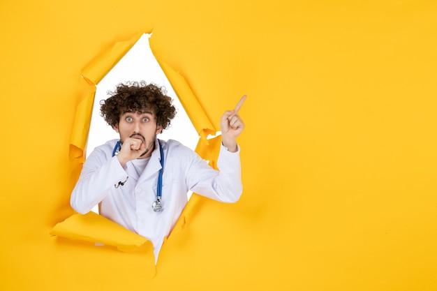 Vooraanzicht mannelijke arts in wit medisch pak op gele gescheurde ziekenhuiskleur virus gezondheidsmedic geneeskunde