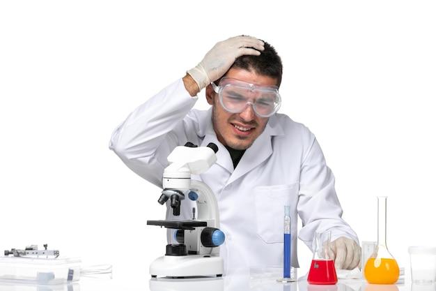 Vooraanzicht mannelijke arts in wit medisch pak op witte ruimte