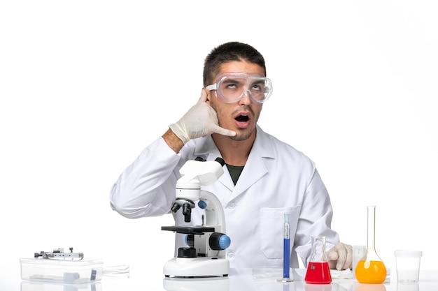 Vooraanzicht mannelijke arts in wit medisch pak poseren op witte ruimte
