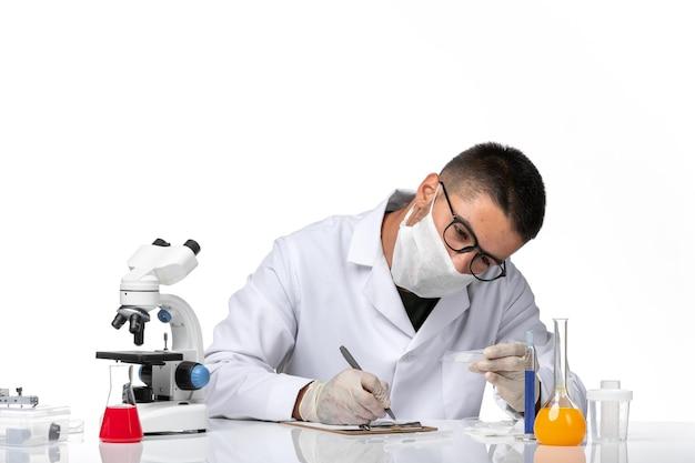 Vooraanzicht mannelijke arts in wit medisch pak werken en schrijven op witte ruimte