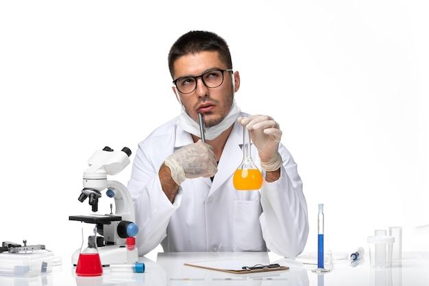 Vooraanzicht mannelijke arts in witte medische pak en met masker werken met oplossing denken op witte ruimte
