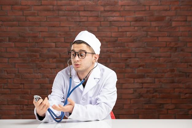 Vooraanzicht mannelijke arts in witte medische pak met een stethoscoop