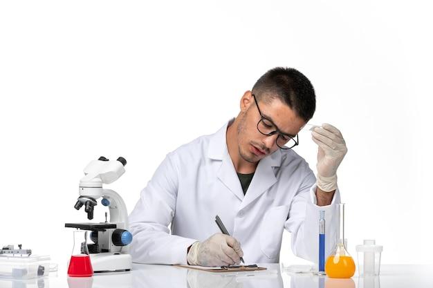 Vooraanzicht mannelijke arts in witte medische pak werken met oplossingen op lichte witte ruimte