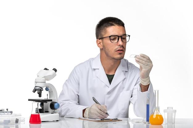 Vooraanzicht mannelijke arts in witte medische pak werken met oplossingen op witte ruimte