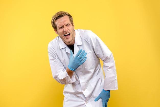 Vooraanzicht mannelijke arts kwetste zijn hand op gele achtergrond medic gezondheid covid pandemie