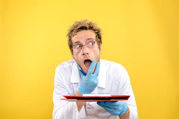 Vooraanzicht mannelijke arts met aantekeningen over de gele achtergrond gezondheid covid-menselijke dokter