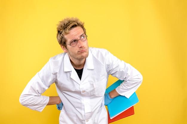 Vooraanzicht mannelijke arts met analyses op gele achtergrondgezondheid menselijke covid-arts Gratis Foto