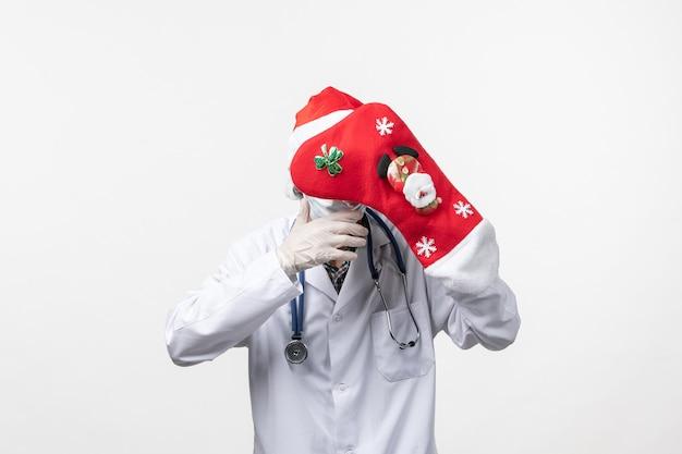 Vooraanzicht mannelijke arts met grote rode sok op witte muur virus covid- kerstmis