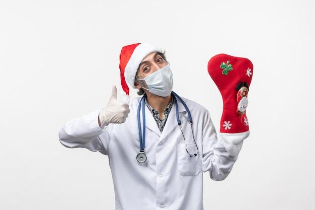 Vooraanzicht mannelijke arts met grote vakantiesok op witte muur virus covid- kerstmis