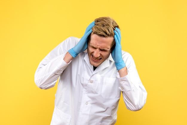 Vooraanzicht mannelijke arts met hoofdpijn op gele achtergrond covid-menselijke emotie medic