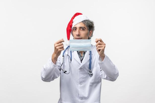 Vooraanzicht mannelijke arts met masker nieuwjaar vakantie virus covid