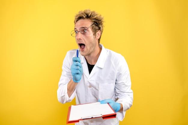 Vooraanzicht mannelijke arts met notities over gele achtergrond gezondheid covid-medic mens