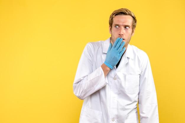 Vooraanzicht mannelijke arts met verlegen gezicht op gele achtergrond gezondheid medic covid-pandemie