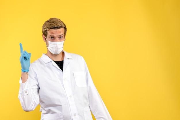 Vooraanzicht mannelijke arts op gele achtergrond pandemisch covid gezondheidsvirus