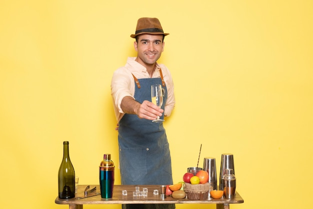 Vooraanzicht mannelijke barman die een drankje maakt op gele muur nacht alcohol bar club mannelijke drank
