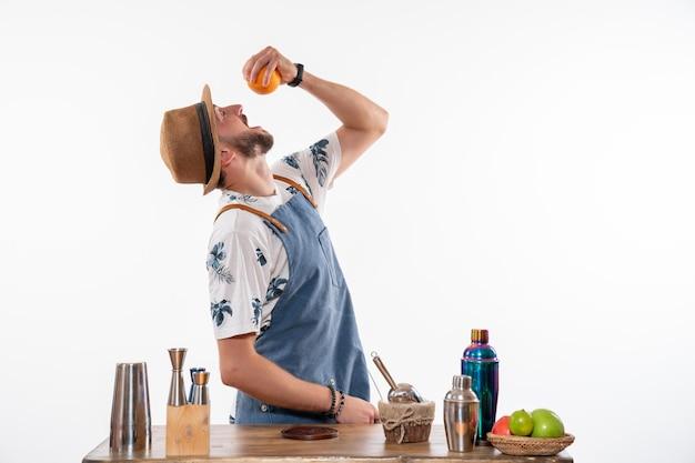 Vooraanzicht mannelijke barman die sinaasappel probeert en drank maakt op witte muur, baanbar, alcoholclub, nachtdrankservice