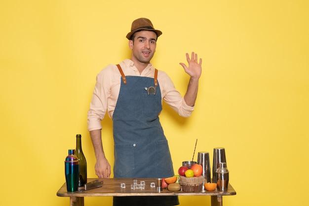 Vooraanzicht mannelijke barman die voor het bureau staat met drankjes en fruit op gele muur, drinkbar, nachtclubsap